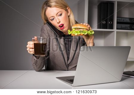 Busy woman talking on the phone while having burger and coffee for lunch