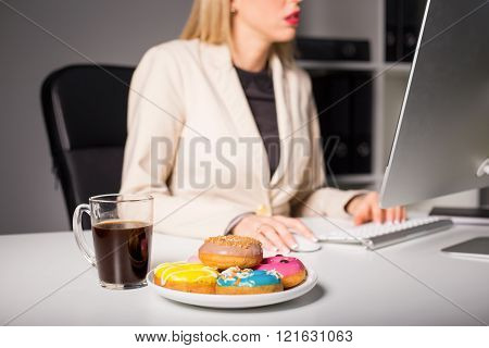 Woman in office with coffee and donuts
