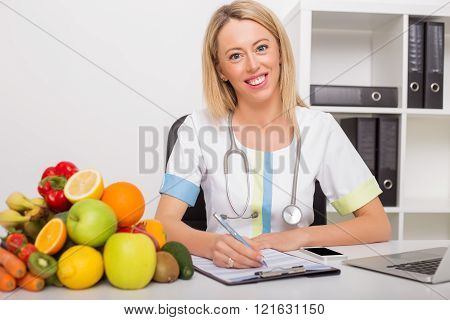 Health doctor in her office with vegetables and fruits