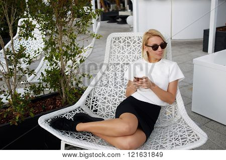 Charming blonde female is looking away while is sitting in comfortable chair with mobile phone