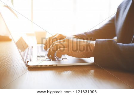 Closeup of businessman is keyboarding on portable net-book while is sitting in modern office