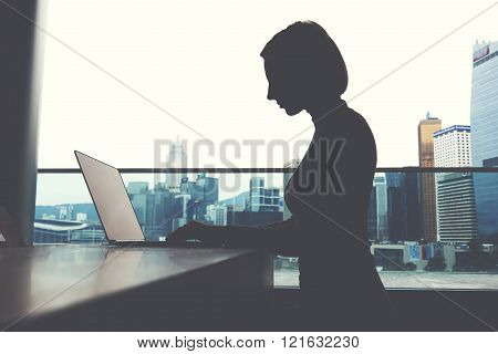 Silhouette of a woman is keyboarding on net-book, while is sitting in office interior