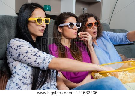 Three girlfriends looking scared while watching a movie