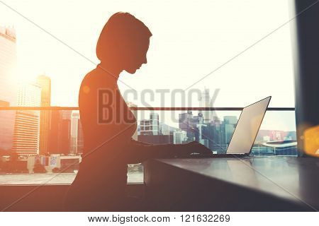 Young businesswoman is typing text message in network via laptop computer