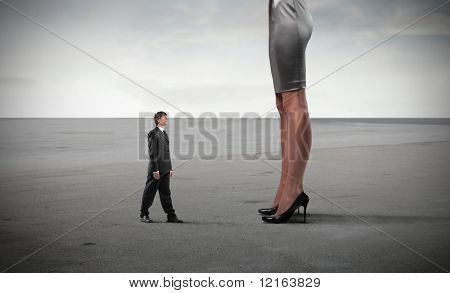Tiny businessman standing in front of huge woman's legs