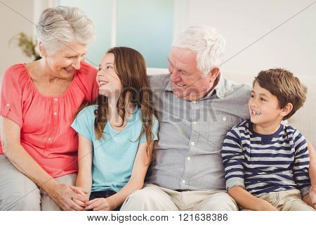 Grandparents and grandchildren sitting together on sofa in living room