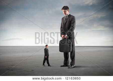Tiny businessman standing in front of a giant one