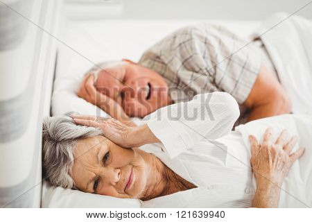 Senior woman covering her ears while man snoring in bed