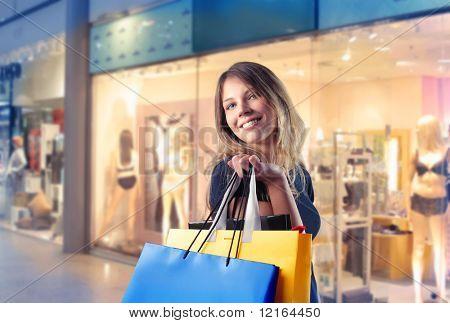 Lächelnde Frau, die einige Einkaufstaschen mit Geschäften auf dem Hintergrund