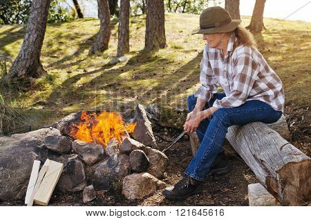 Senior Woman By A Camp Fire