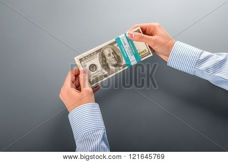 Womans' hand holding dollar bundle.