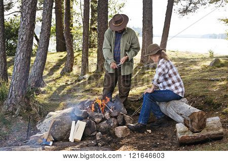 man paring sticks for grilling
