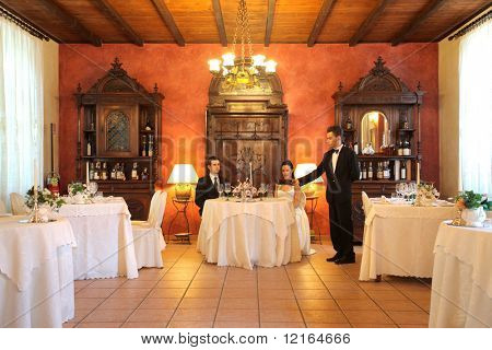 Young waiter serving some wine to a newly married couple