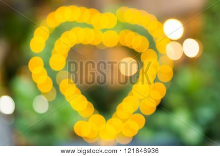 Blurred Of Yellow Light Bulb In Heart Shape.