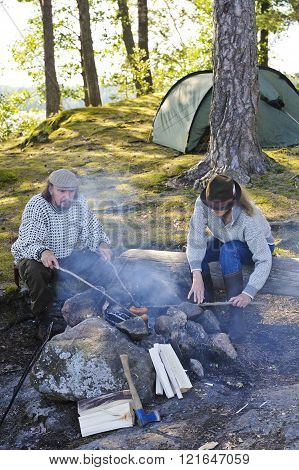 grilling sausages over camp fire