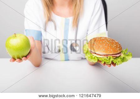 Health professional with apple and burger