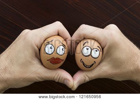 Girl And Boy Egg Face In Man Hand