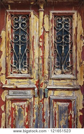 Closeup on an old and neglected wooden door with ironwork windows