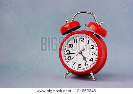 Red Retro Alarm Clock On A Blue Background.