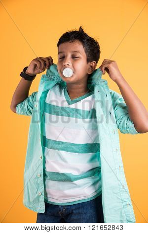 Boy blowing a bubble, indian boy chewing bubble gum and making a balloon, asian boy and chewing gum