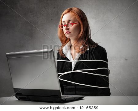 Bound businesswoman sitting in front of a laptop