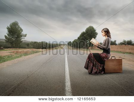 Woman sitting on a suitcase on a countryside road and reading a book
