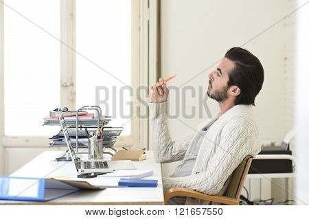 young attractive student preparing university project or hipster style freelancer businessman working with laptop computer analyzing project at home office studio corporate portrait
