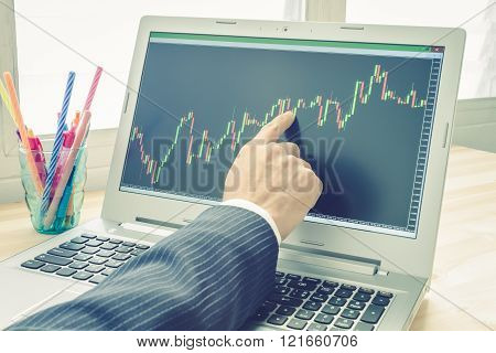 Businessman is pointing stock graph . Technical analysis stock by professional trader with pen in vintage style