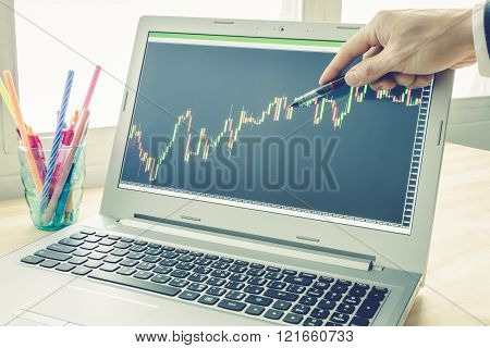 Businessman is pointing stock graph. Technical analysis stock by professional trader with pen in right hand in vintage style