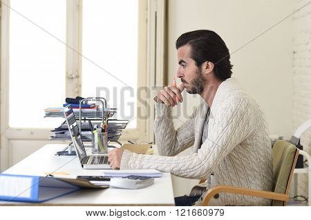 young attractive student preparing university project or hipster style freelancer businessman working with laptop computer analyzing project at home office studio