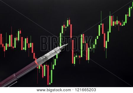 Stock Or Forex Graph Or Candlestick Chart And Pen On Black Screen