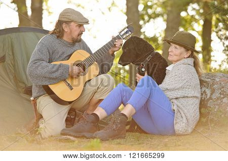 Senior couple enjoying some music outside their tent in evening light. Man plays guitar. They have their pet curly coated retriever with them. Natural lens flare.