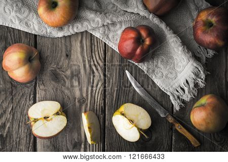 Red apples and apple halves on a wooden table horizontal
