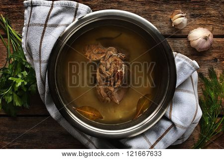 Meat broth from beef in a metal pan on the wooden table