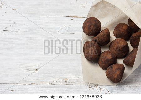 Chocolate truffle candies in the paper packing on the white wooden table horizontal