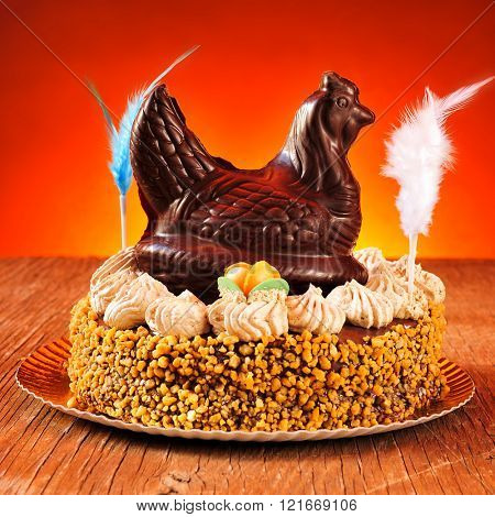 a mona de pascua, a cake eaten in Spain on Easter Monday, ornamented with feathers and a chocolate chicken, on a rustic wooden surface