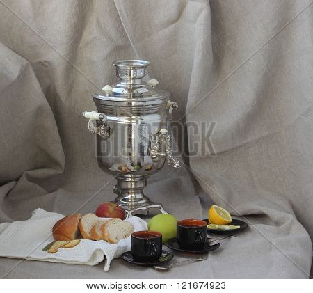 Stil life with a samovar, two cups of tea, apples, lemon and sliced bread.