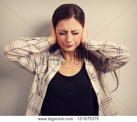 Stressed unhappy business woman closed ears the hands because not want the hear any sounds