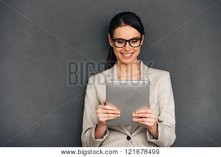 Enjoying her new digital tablet. Beautiful young cheerful businesswoman holding digital tablet and looking at it with smile while standing against grey background
