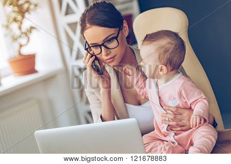 Let me talk to your business partner! Young beautiful businesswoman talking on mobile phone and looking at laptop while sitting with her baby girl at her working place
