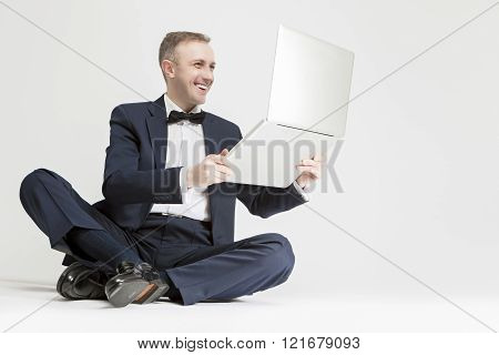 Young Smiling Caucasian Blond Man Holding  Laptop And Smiling. Sitting Against White