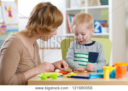Woman and kid boy playing with plasticine at table in nursery room