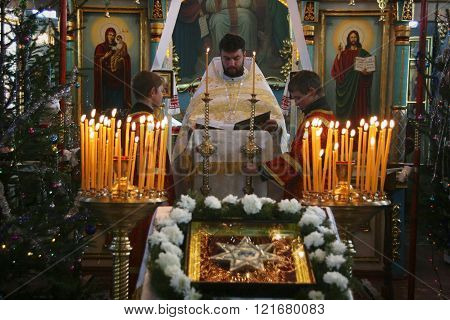 VOYUTYN UKRAINE - JANUARY 08: Orthodox priest and little sextons during holiday prayers in Voyutyn on January 08 2009.