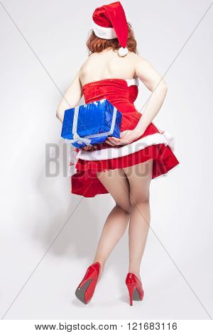 Hot And Sexy Caucasian Female In Santa Hat Holding Gift Box Behind. Isolated On White.