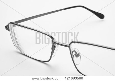 Male eyeglasses macro detail over a white background. Horizontal poster