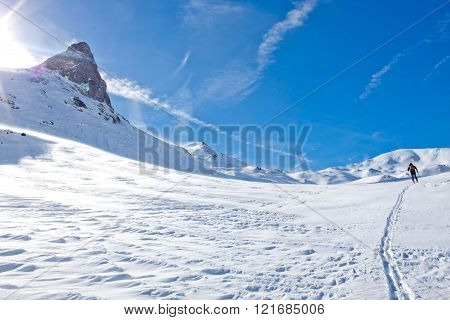 skier going up of a mountainin a sunny day