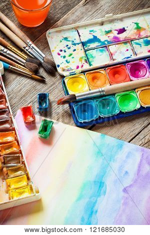 Watercolor paints, brushes for painting and paper sheet of painting on old wooden background.