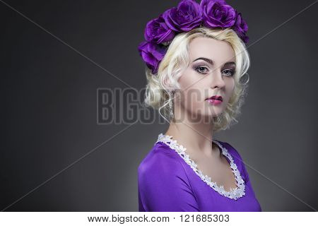 Beauty and Fashion Concept and Ideas. Blond Caucasian Female Posing in Purple Dress. Crowned with Fl