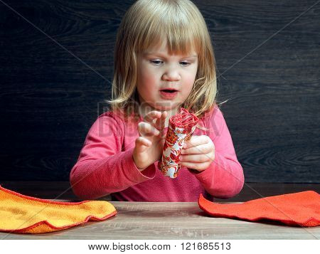 Little girl is learning to put things carefully - towels