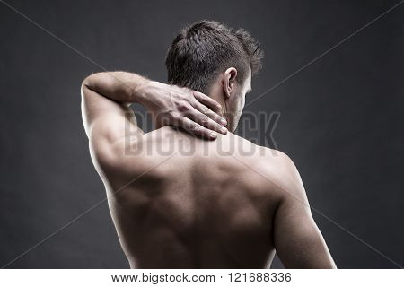 Pain in the neck. Man with backache. Muscular male body. Handsome bodybuilder posing on gray background. Low key close up studio shot. Middle part of the body